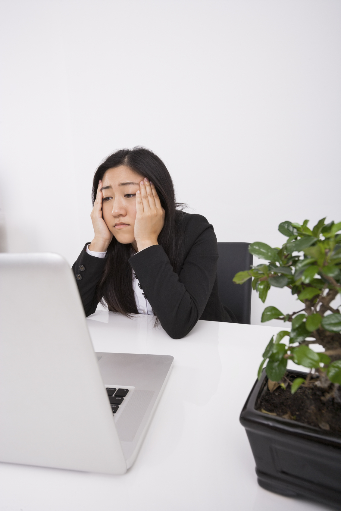Stressed businesswoman looking at laptop in office