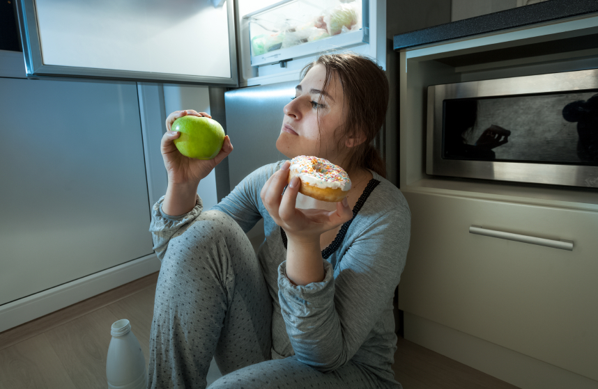 woman choosing between apple and donut at evening lunch